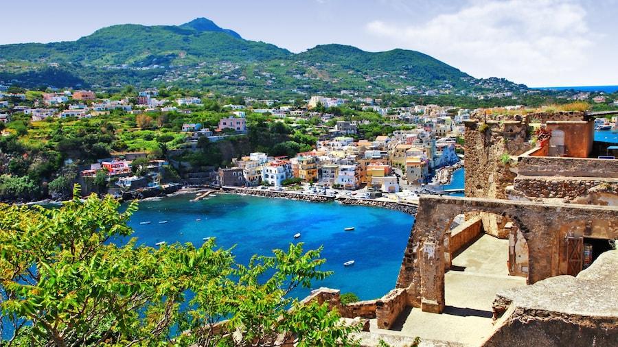 Ischia inclusief een baai of haven, historische architectuur en vervallen gebouwen