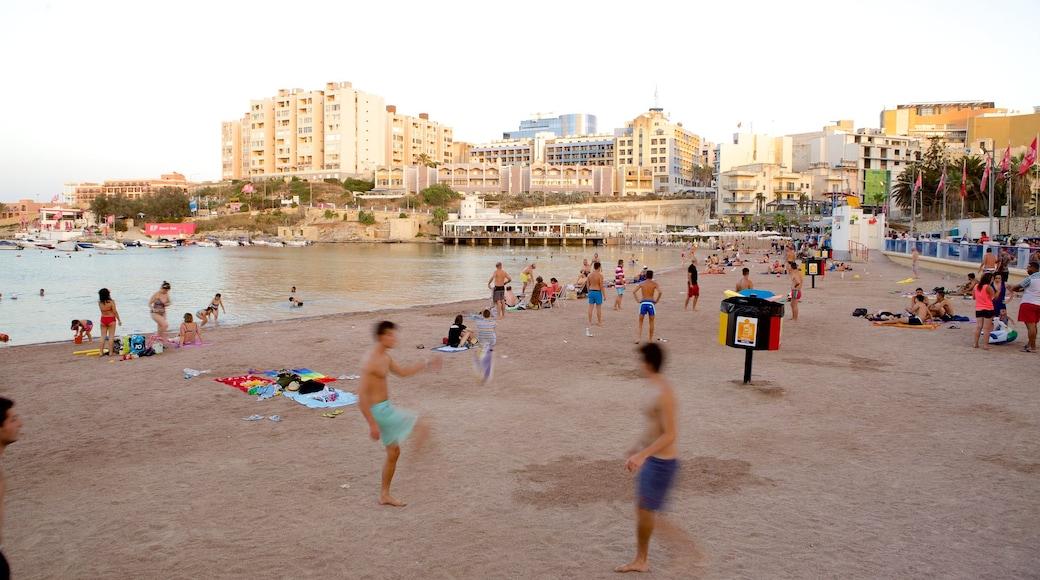 St George\'s Beach das einen Sandstrand sowie große Menschengruppe