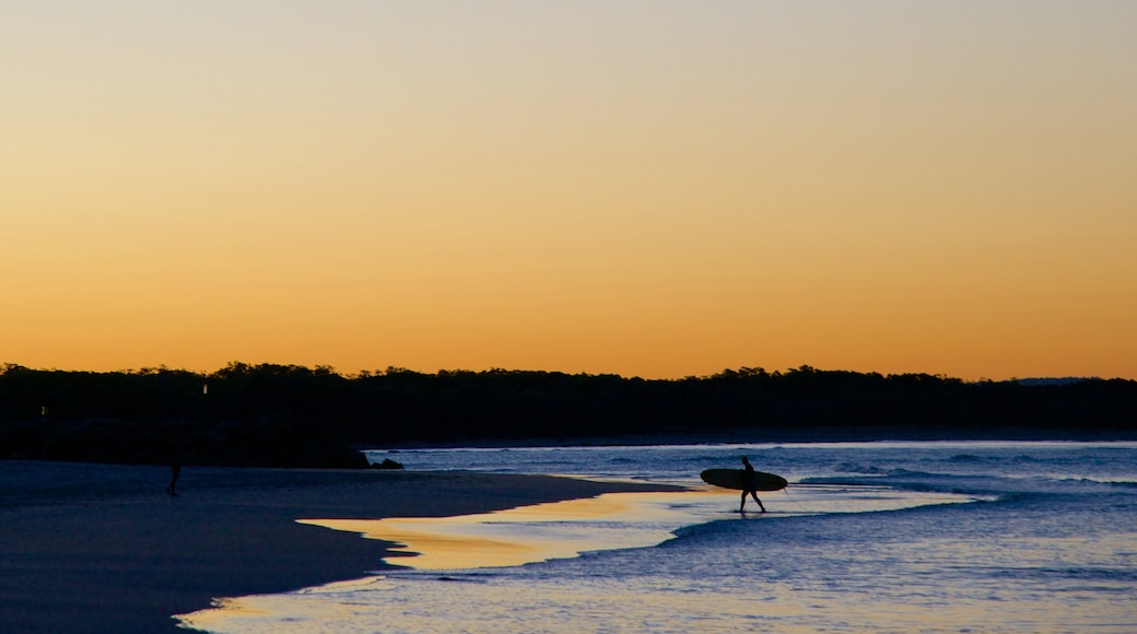 Noosa Beach showing a sandy beach, a sunset and surfing