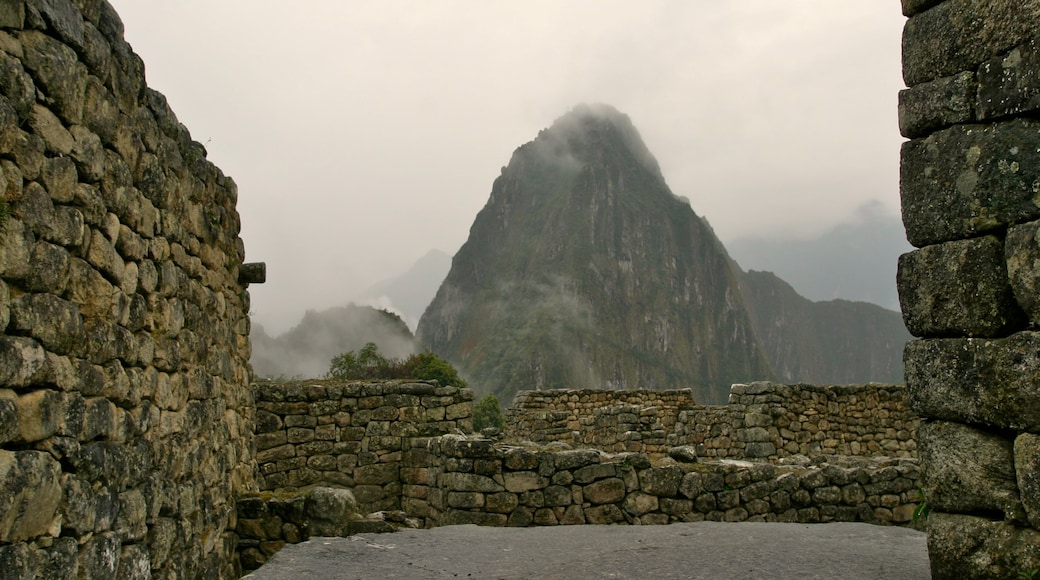 Huayna Picchu showing a ruin, mist or fog and mountains