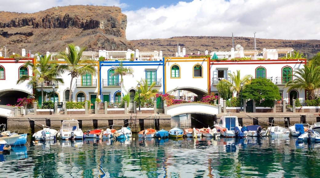 Mogán que incluye una bahía o un puerto, embarcaciones y una localidad costera