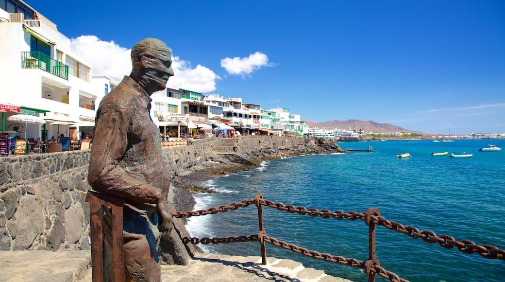 Playa Blanca welches beinhaltet Küstenort, Felsküste und Statue oder Skulptur