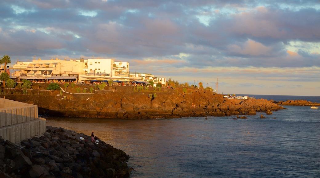 Puerto del Carmen mostrando una localidad costera, un atardecer y litoral rocoso