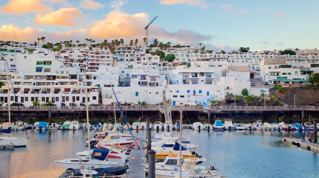 Puerto del Carmen ofreciendo una bahía o un puerto, embarcaciones y una localidad costera