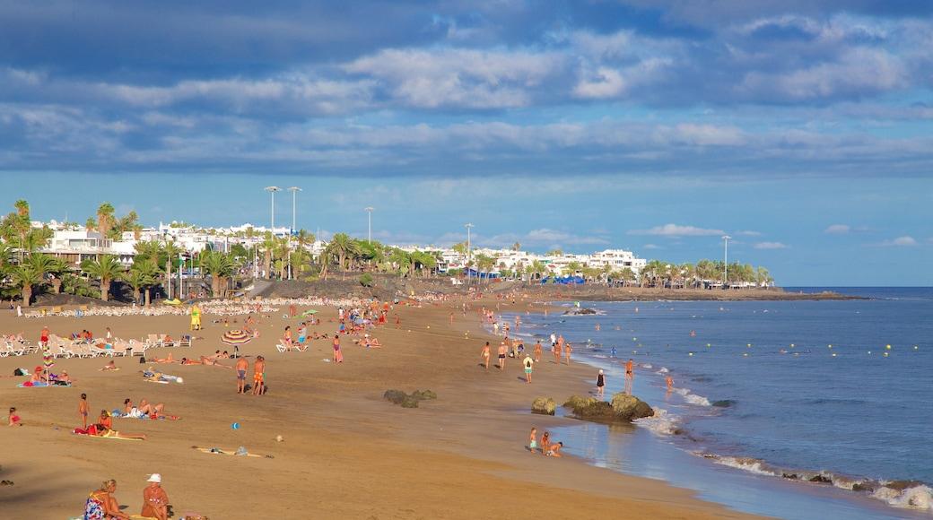 Strand Puerto del Carmen mit einem allgemeine Küstenansicht und Sandstrand sowie große Menschengruppe
