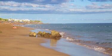Puerto del Carmen Beach which includes a sandy beach and general coastal views