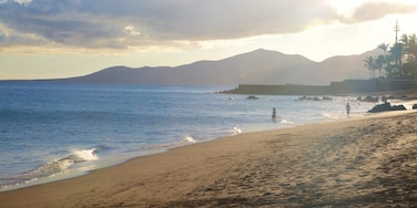 Puerto del Carmen Beach featuring a sunset, general coastal views and a beach