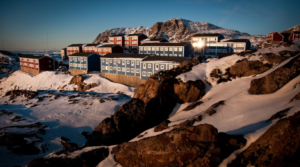Sisimiut which includes a sunset, a small town or village and snow