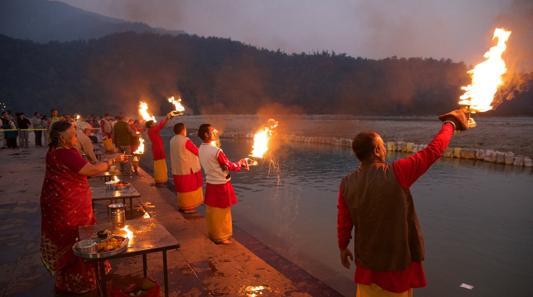 Triveni Ghat featuring religious aspects and a sunset as well as a small group of people