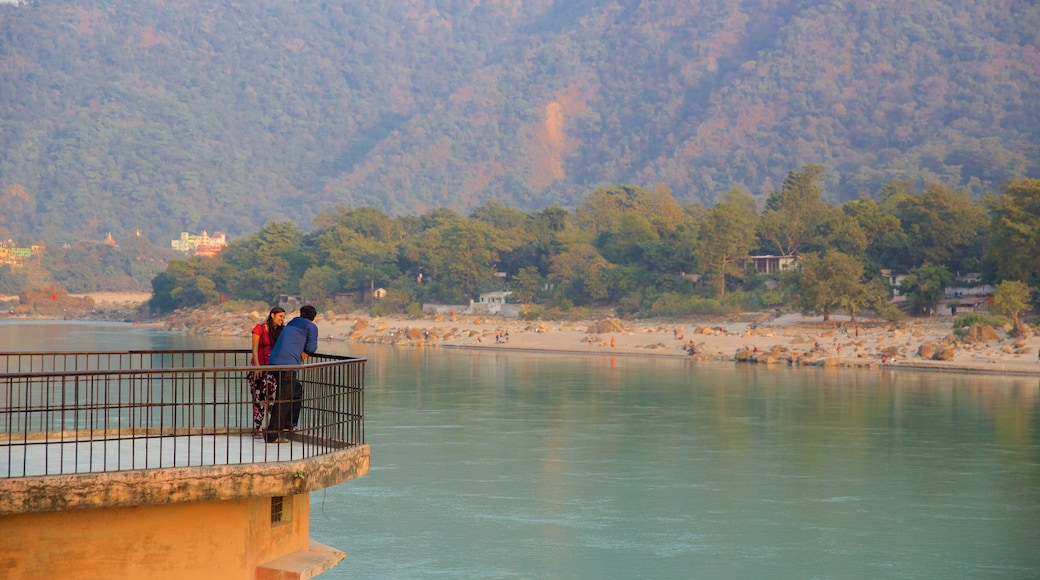 Ram Jhula showing a river or creek and tranquil scenes as well as a small group of people