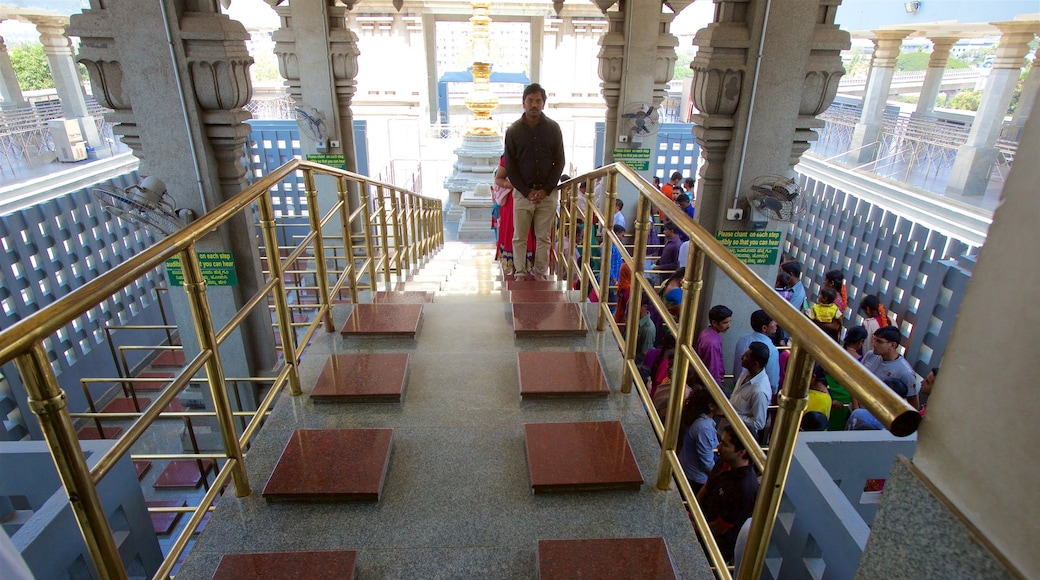 ISKCON Temple which includes a temple or place of worship and interior views as well as a small group of people