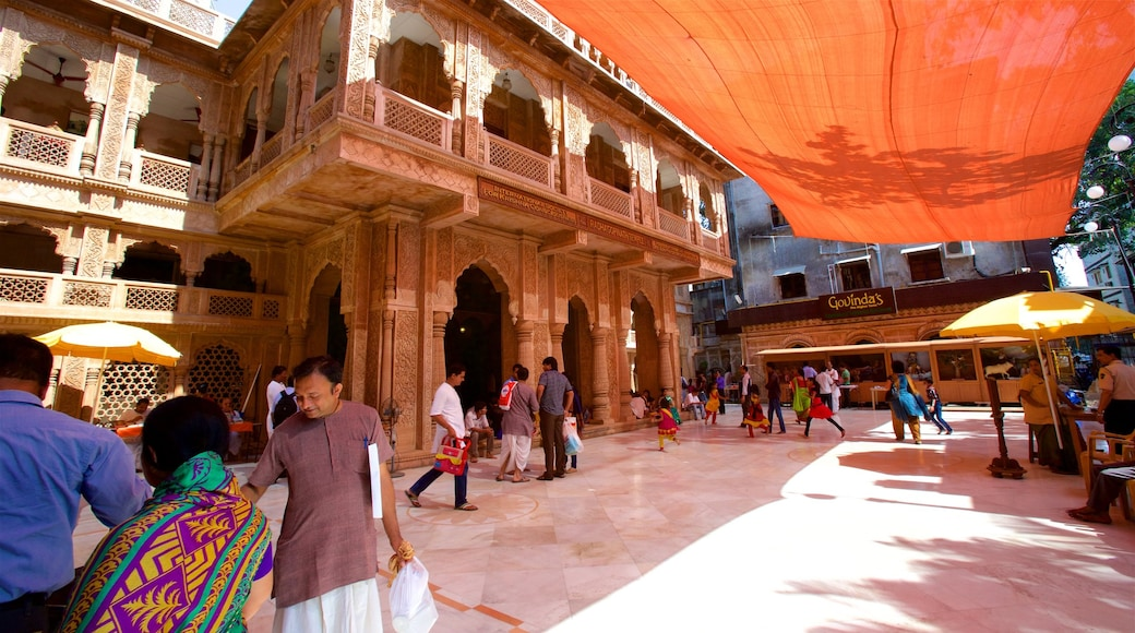 ISKCON Temple featuring a temple or place of worship as well as a small group of people