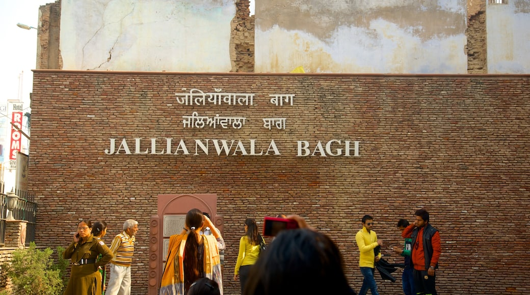Jallianwala Bagh featuring signage as well as a small group of people