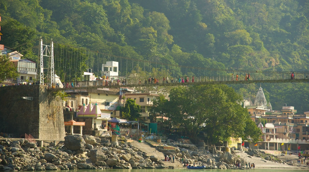 Lakshman Jhula which includes a river or creek, a small town or village and a bridge