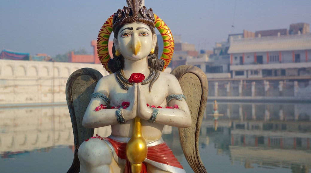 Durgiana Temple featuring a lake or waterhole and a statue or sculpture