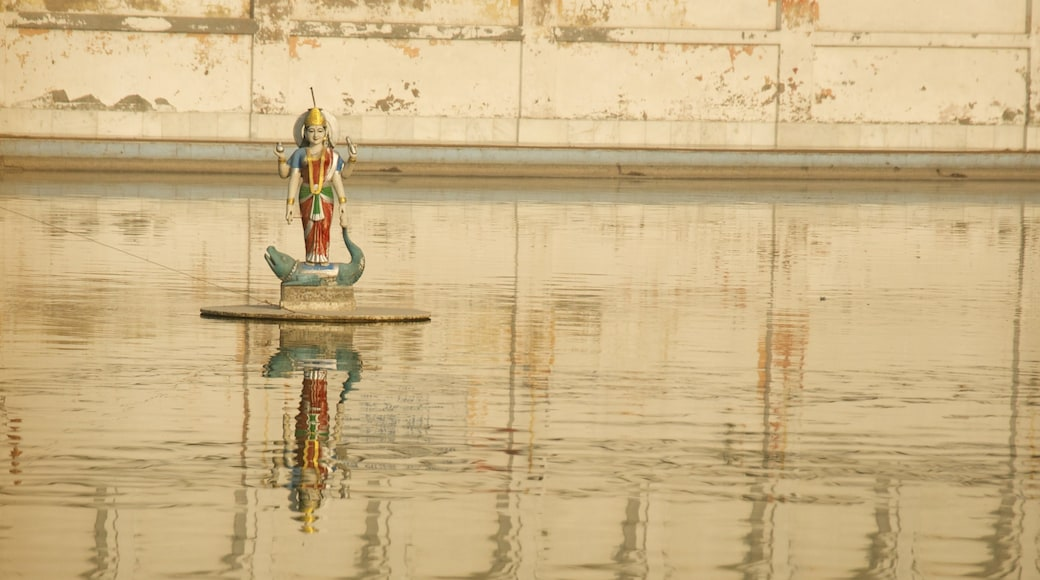 Durgiana Temple which includes a statue or sculpture and a lake or waterhole