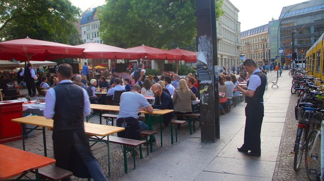 Plaza Hackescher Markt que incluye comidas al aire libre y también un gran grupo de personas