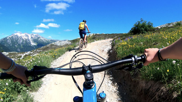 two people riding bikes in the mountains