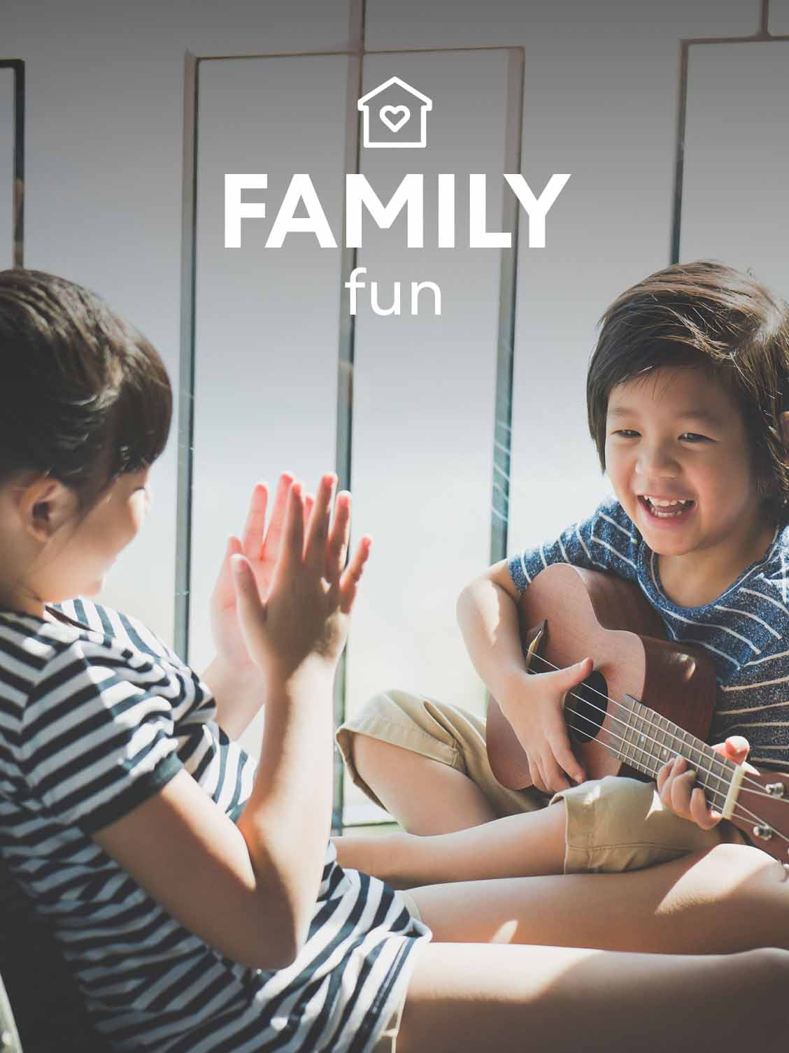 Two children are sitting and having fun. One child is playing the guitar. A superimposed title reads: Family fun.