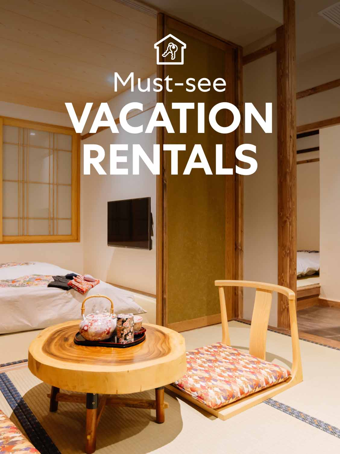 Interior view of a Japanese-style hotel room. Screens are set up to separate areas. A small floor table and chair sit in the forefront, a low bed in the background. A superimposed title reads: Must-see vacation rentals.
