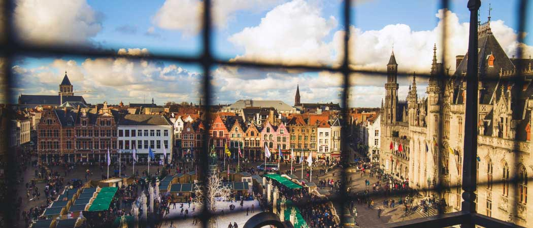 Aerial view of Bruges, Belgium city center, shot through bars of an upper terrace fence.