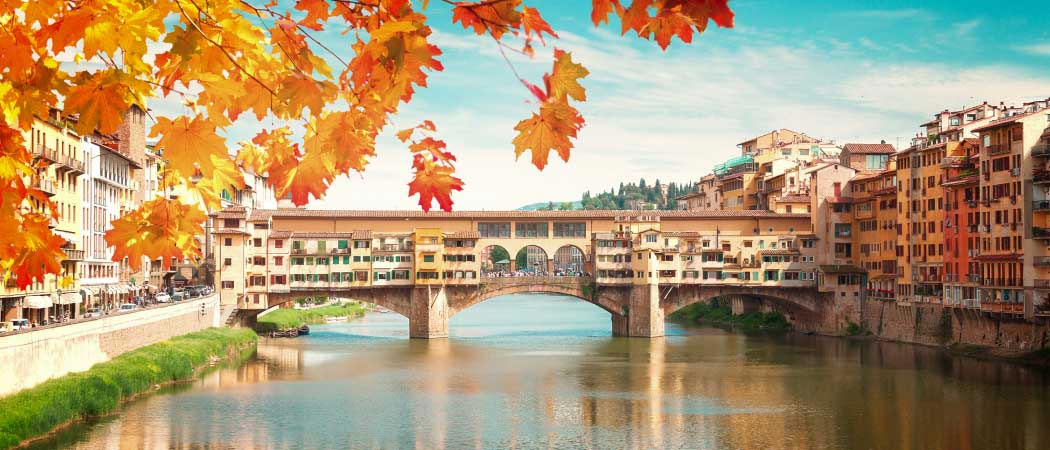 A covered foot bridge crossing a canal in Florence, Italy. A tree with Fall colored leaves hangs in the foreground.