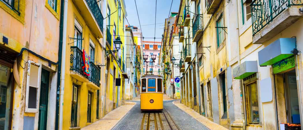 Ground view of a colorful street on a hill in Lisbon, Portugal, with a street car heading down the hill and facing the camera.