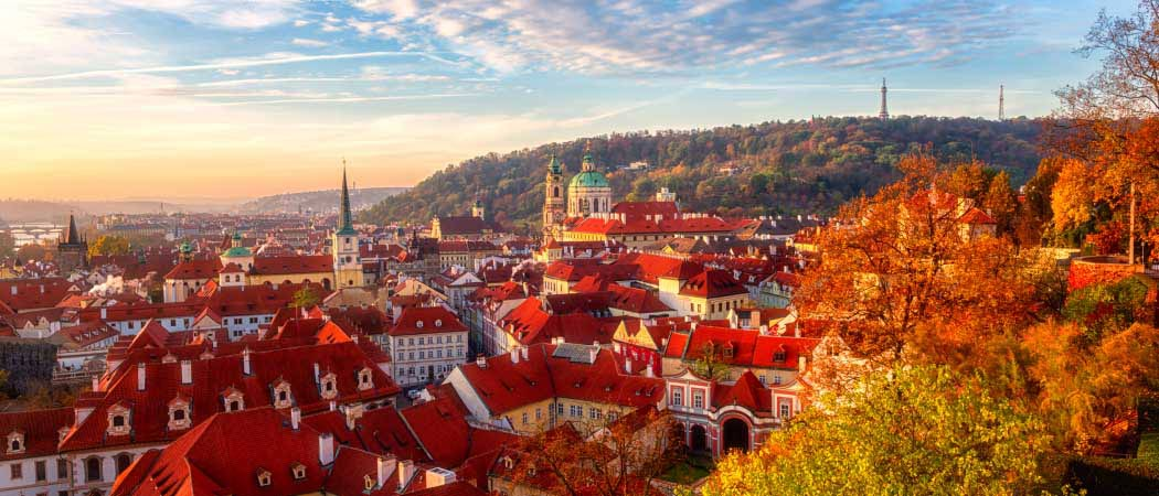 Aerial view of Prague, Czech Republic in the Fall. Trees with orange colored leafs hover in the foreground.