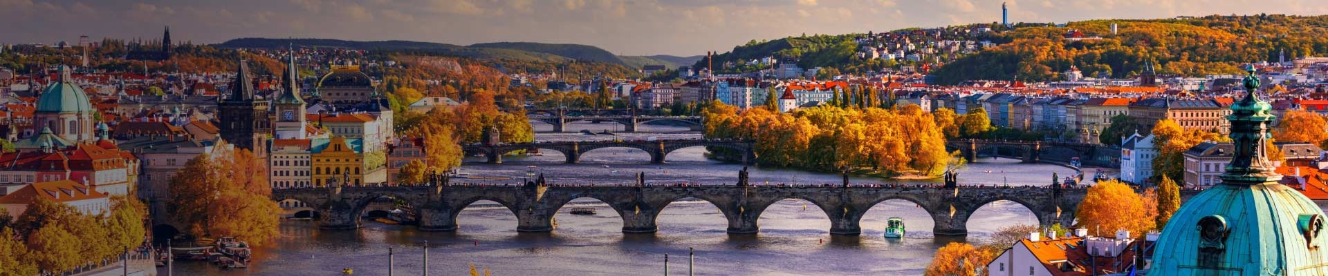 Aerial view of Prague, Czech Republic in the Fall. Trees with orange colored leaves line either side of the Vltava River.