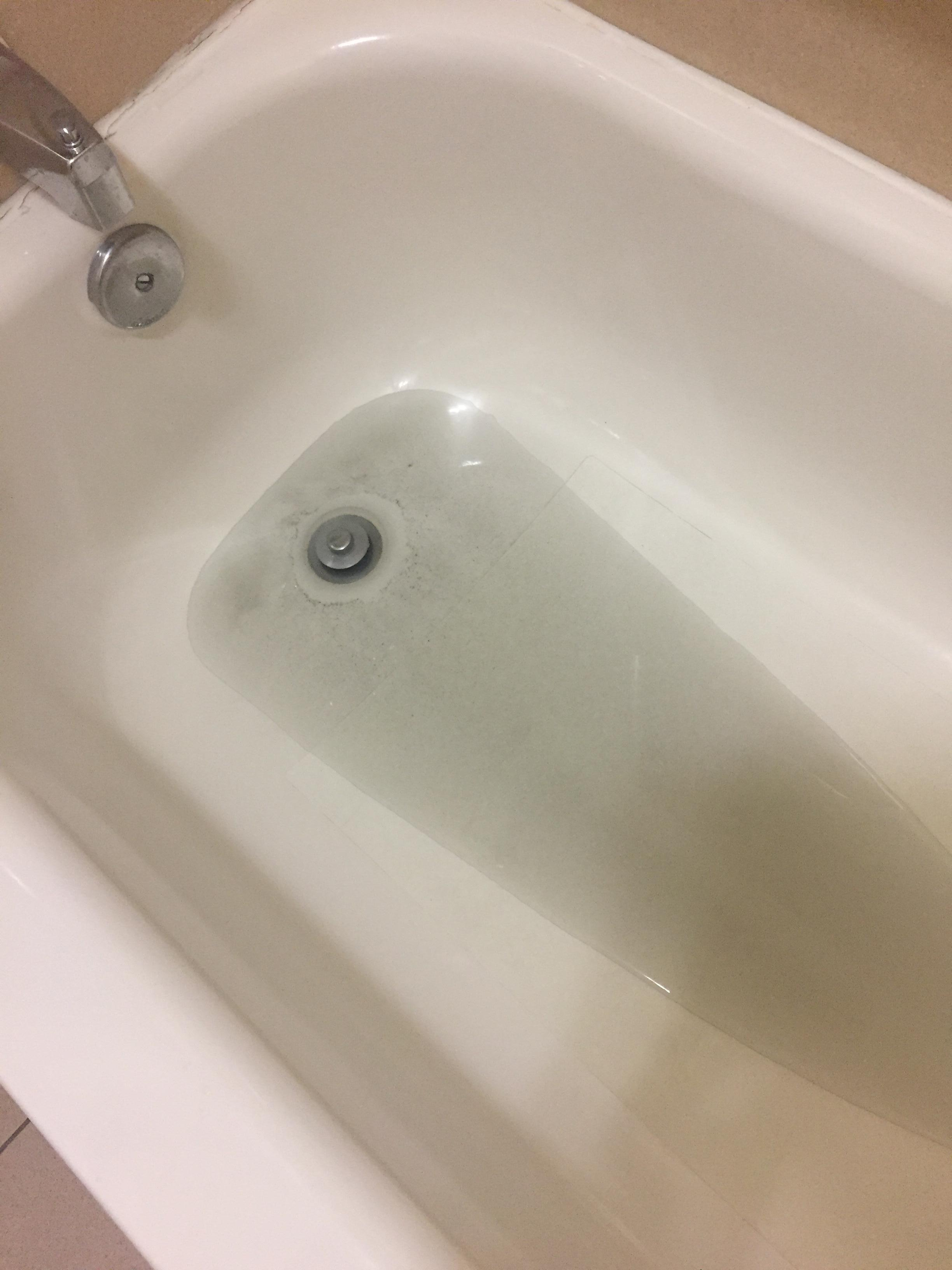 Black shower water that bubbled up from next door