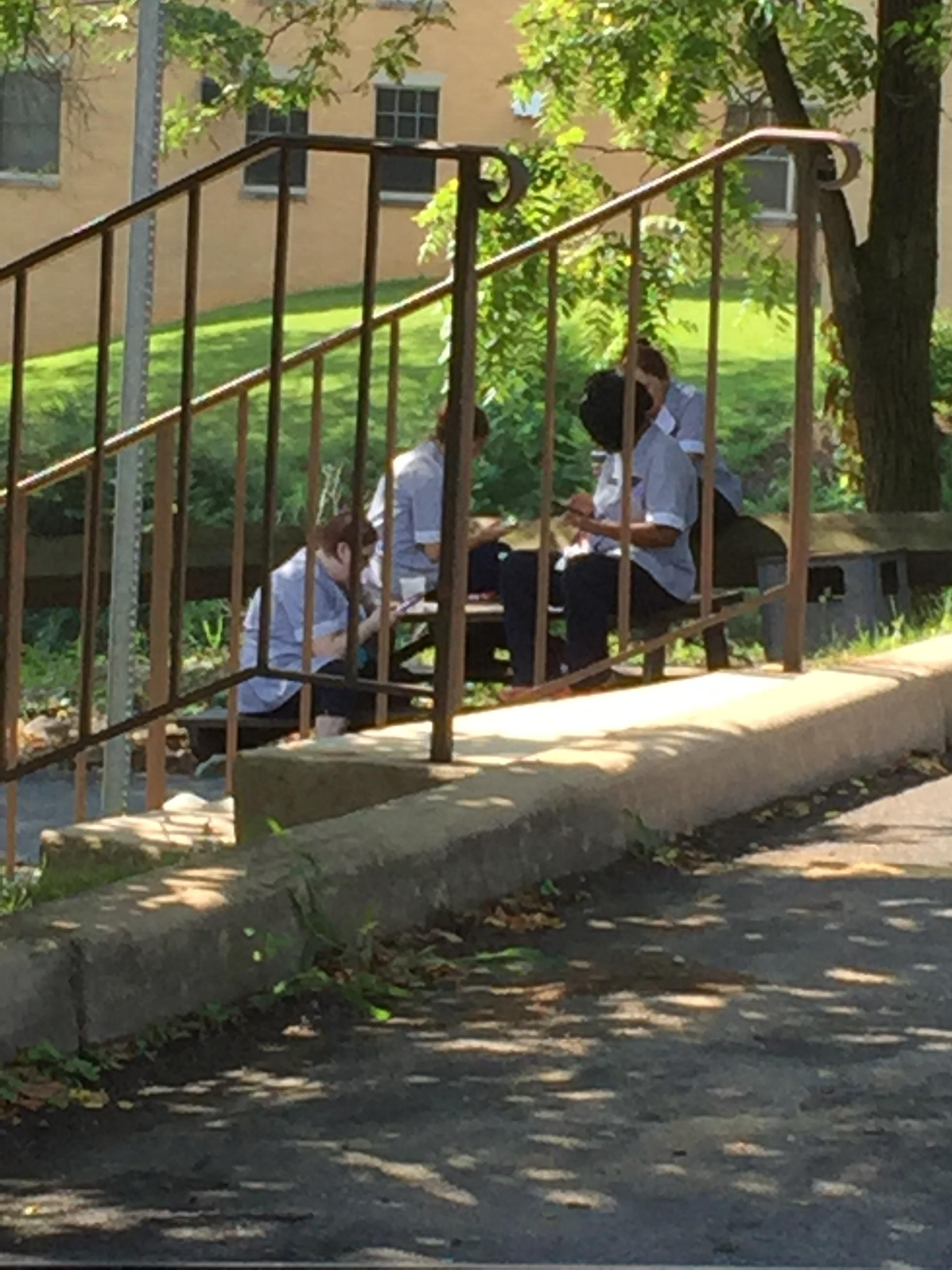 Housekeepers sitting on phones and smoking adjacent to the parking lot.