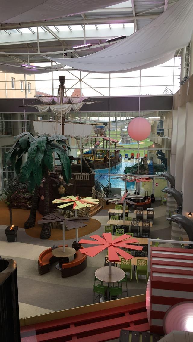 Grande salle avec aire de jeu et piscine en arrière plan