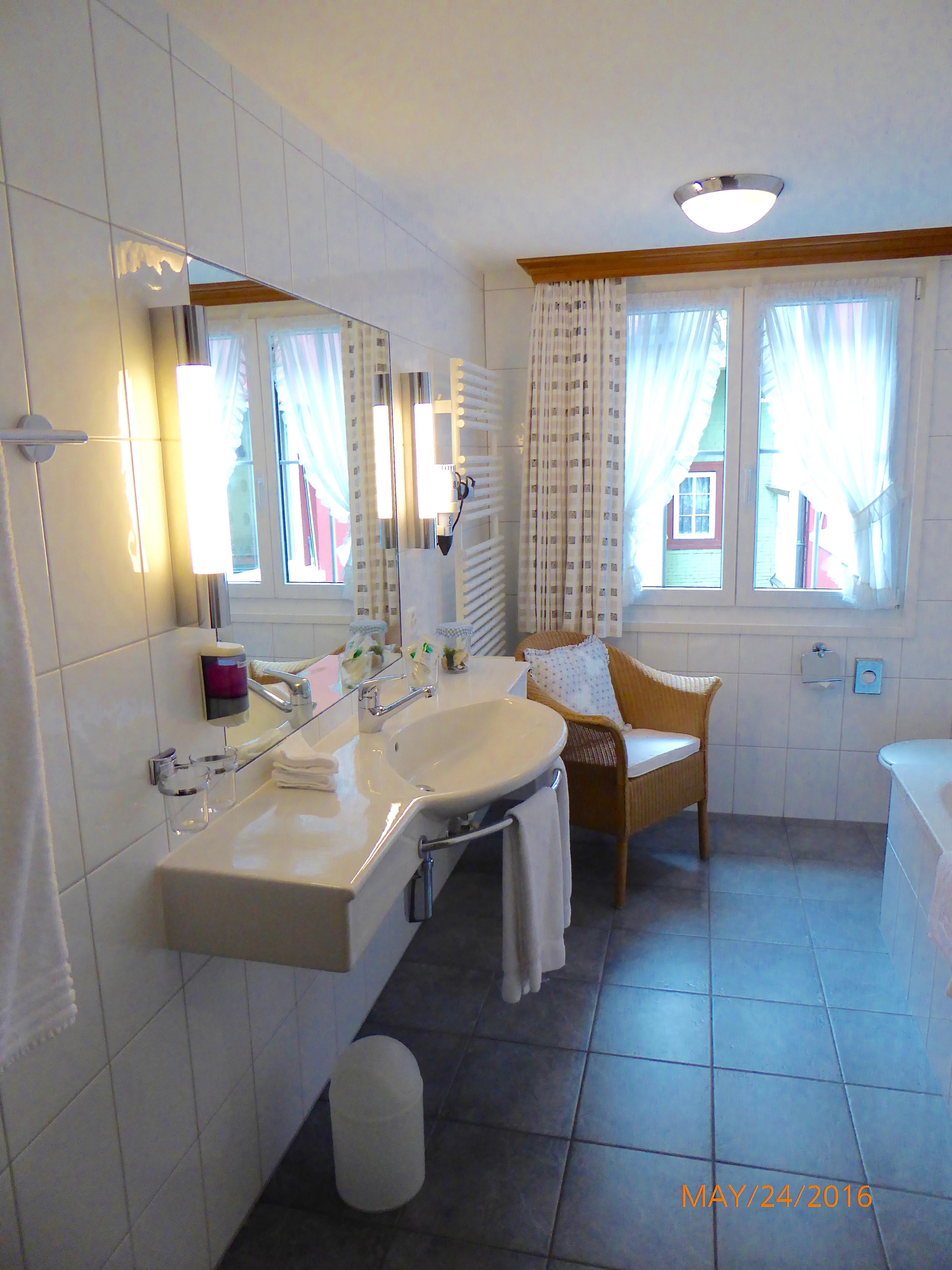 Sink area. Bathtub across from sink, shower in one corner, toilet in corner by window