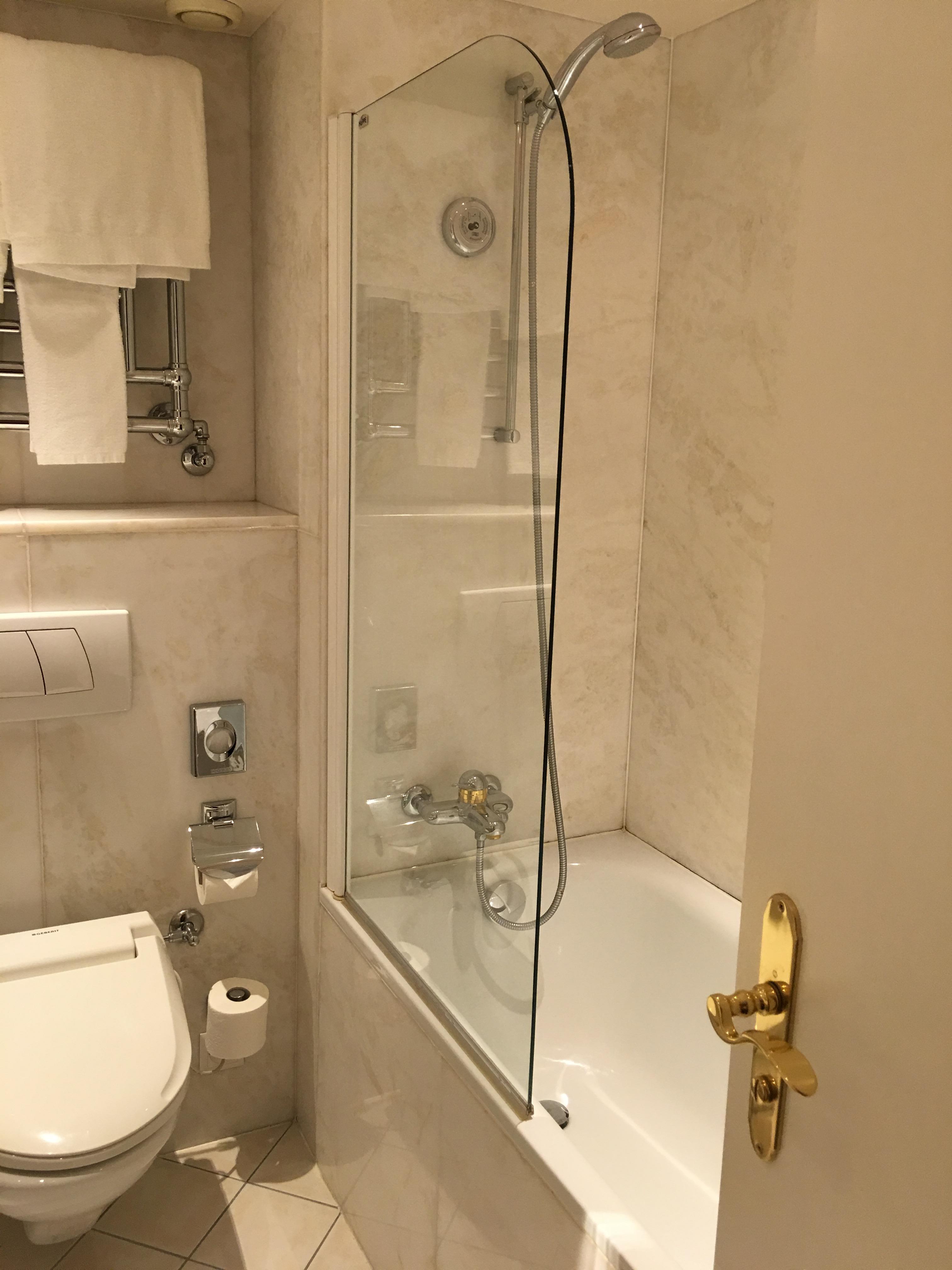 Half shower door not practical. Towel bar above toilet is a dangerous reach from shower. Need hook on back of door.
